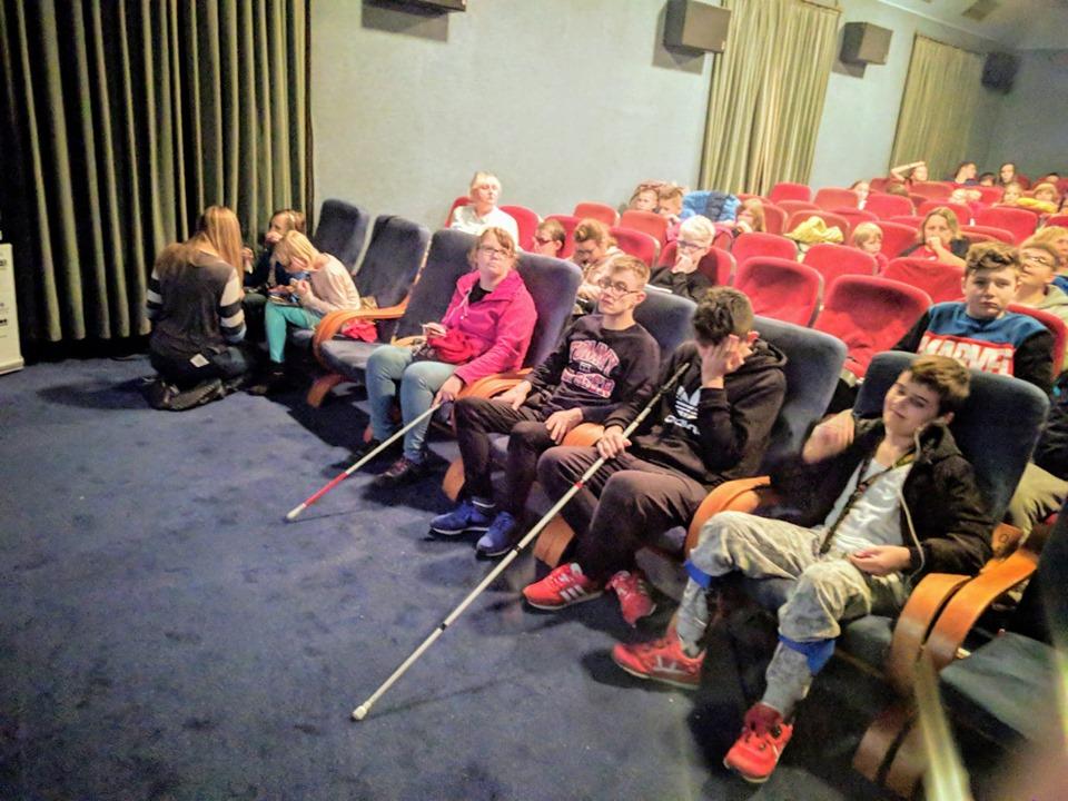 Pierwszy rząd widowni w sali kinowej. Uśmiechnięte dzieci czekają na film.