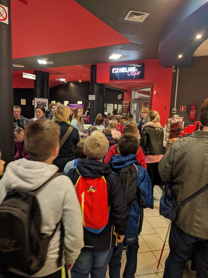 Widzowie czekają na pokaz w kinowym korytarzu.