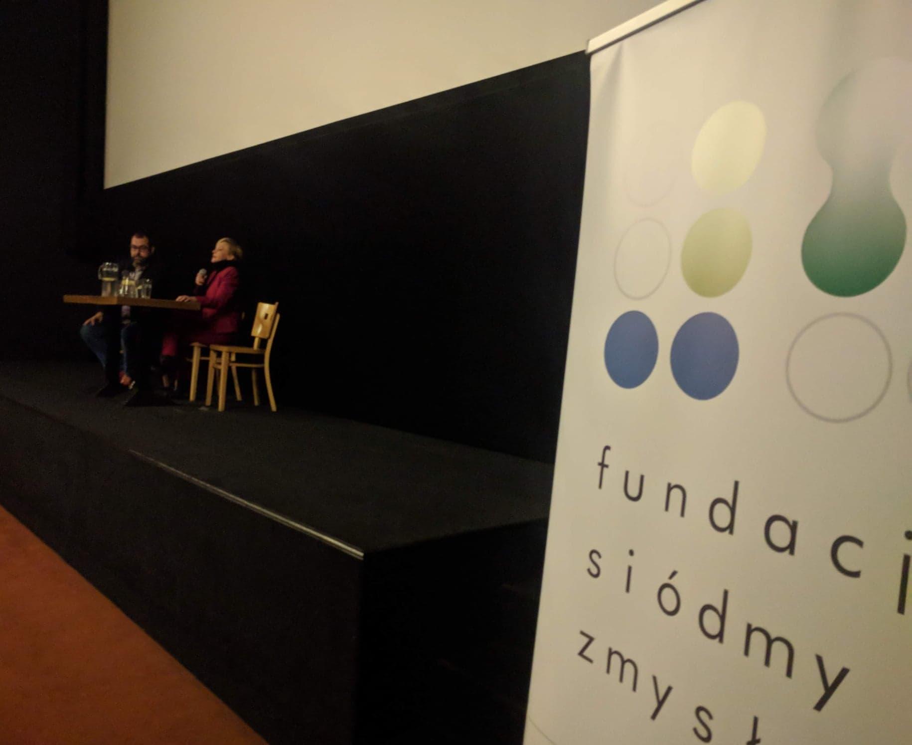 Scena pod białym kinowym ekranem. Przy stoliku siedzą Maciej Gil oraz Barbara Kurzaj. W lewym rogu baner Fundacji Siódmy Zmysł