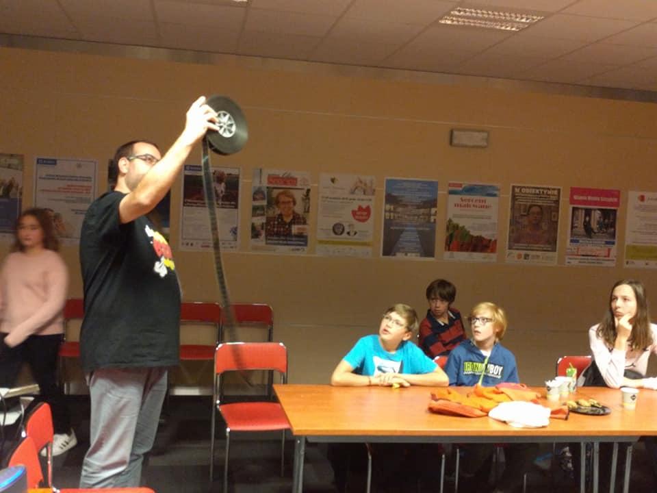 Maciej Gil w wyciągniętej ręce trzyma rolkę z taśmą filmową.