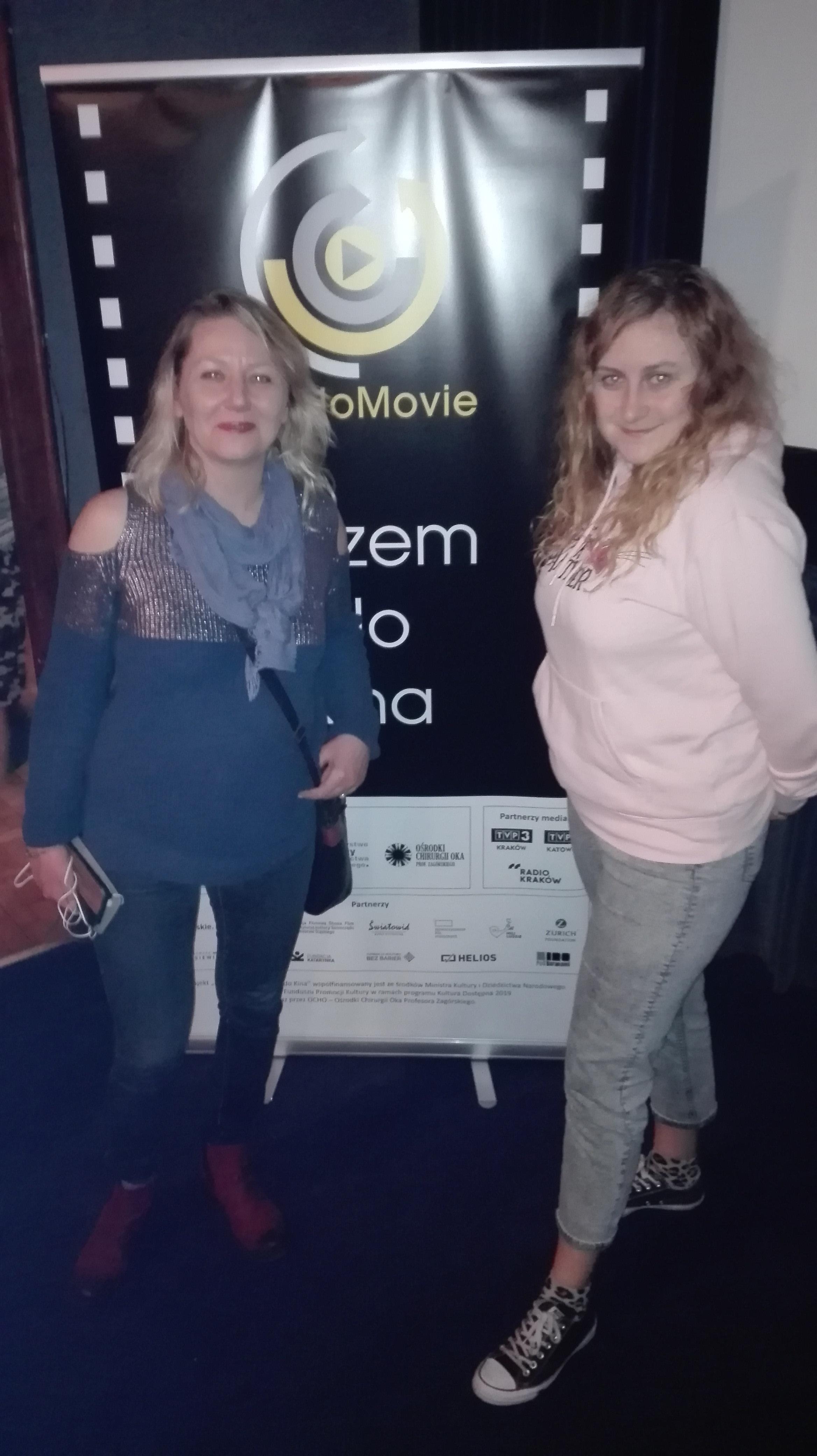 Alicja i Regina stoją na tle plakatu AudioMovie w kinowej sali.