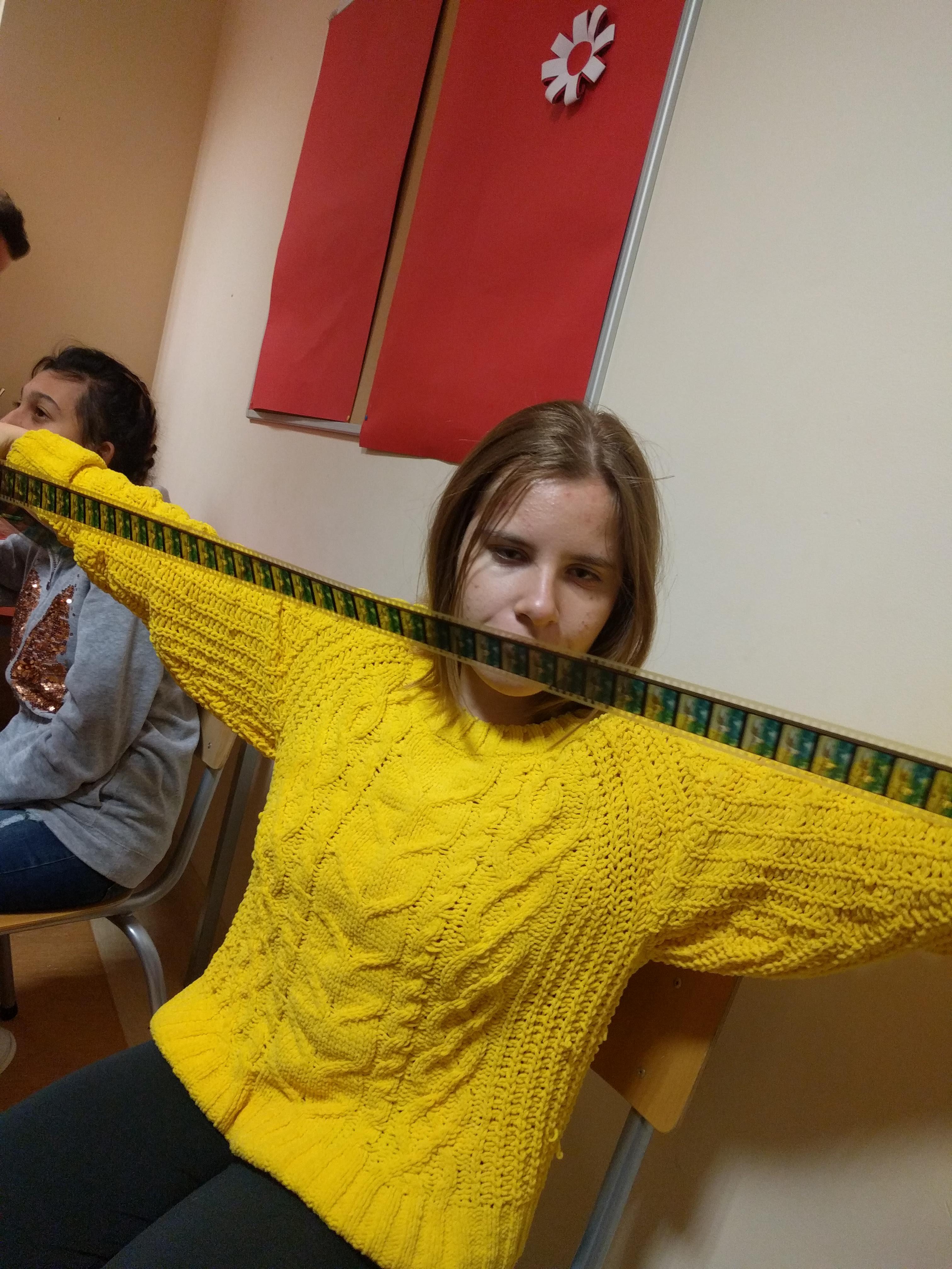 Dziewczyna rozciąga szeroką ręce. trzyma rozwiniętą taśmę filmową.