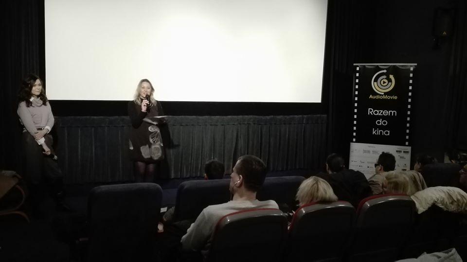 Regina stoi na tle białego ekranu. Nieopodal Magdalena Nieć.